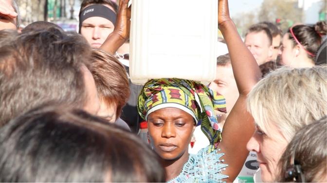 Gambisk kvinna bär vattendunk på huvudet genom Paris maraton